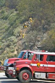 Crews work their way into the brush above Highway 154.