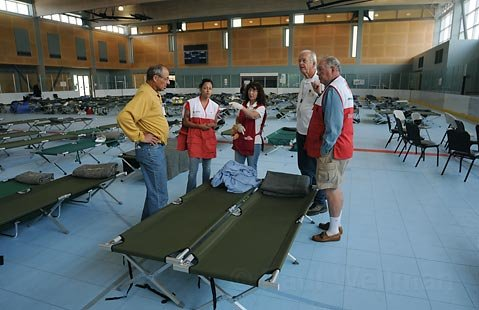 Red Cross volunteers plan the reorganization as many people leave the shelter and go home while the Dos Pueblos High School shelter location closes and consolidates at UCSB's MAC
