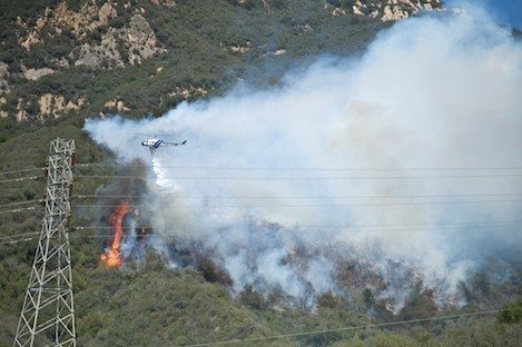Photo clearly depicts start point of the fire. Smoke along the lower horizontal area to the right of the flames outlines the trail. Flames indicate the far west (left) edge of the fire perimeter. Investigators are looking at the 100 yard section of the trail immediately to the right of the flames as the point where the fire started.