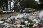 Firefighters extinguish flaming rubbish near Dos Pueblos Canyon on Tuesday morning.