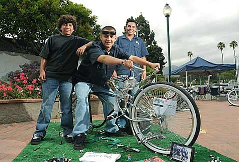 "Christian Solis (center) poses on his bike ""Chameleon"" with brother Enrique (left) and Riding Low Bike Club president Juan Montero (right) during the Lowrider Festival at Earl Warren Showgrounds"
