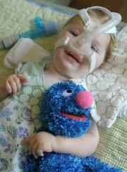 20-month-old Gwendolyn smiles through her respirator when the subject turns to Grover