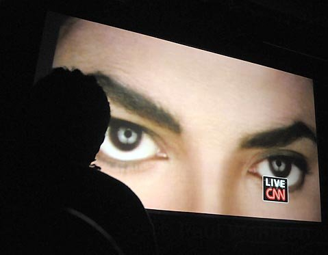 A mourning fan watches the Michael Jackson memorial in the Arlington Theatre via live video feed from the Staples Center July 7, 2009