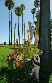 The sculpture donated by artist Morris Bear Squire  a cactus plant with seventeen unique flowers, marked with the names of the deceased, along with one of the deceased pet Max a German shepherd