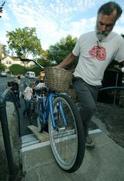 Robert Rainwater brings a beach cruiser up to the secured bike parking area.