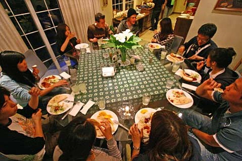 English-language students from around the world share a meal together in Larry and Harriet Kaempf's dining room. For some of these students, it may be the only well-balanced meal they get for the week.
