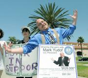 KCSB's Bryan Brown emulates the shoulder-shrugging photo of Mark Yudof on his protest sign that points out the disparity of pay in a time of budget cuts