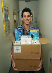 Patrick Krejdovsky, a physician assistant at the Eastside Neighborhood Clinic, holds one of the many boxes of medical supplies donated by DRI