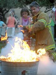 Six-year-old Adelia Hubbard is shown how to use a fire extinguisher by Santa Barbara City Fire Captain Chris Mailes