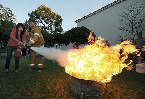 Santa Barbara City Fire Captain Chris Mailes shows willing participants proper fire extinguisher techniques