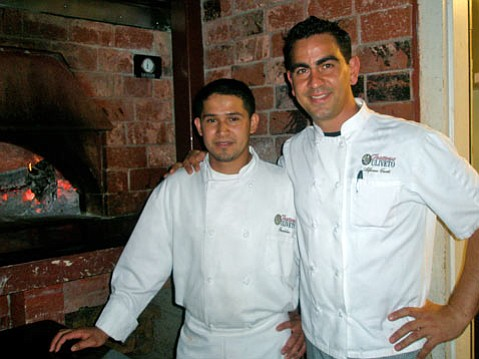 Old-school Italian:  Trattoria Uliveto's Chef Alfonso Curti (top right) and his assistant Franklin pose in front of the wood-burning oven, which churns out delicious pizzas and roasted chicken.