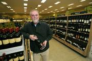 General Manager John Jurey holds a bottle of Consilience 2006 Pinot Noir, one of the many local labels in Whole Foods wine section.