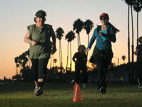 Body Boot Camp regulars Lisa Grossman (left) and Kelly DiGrazia feel the burn while working out at Shoreline Park. Both women have been exercising with the program for five years, and Grossman has lost 50 pounds to date.