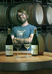 Santa Barbara Winery's Assistant Winemaker Ryan Ralston proudly shows off some red and white selections, both of which were winners with this year's readers.