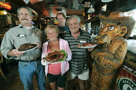 "Woody's regulars Craig, Dorothy, ""Otto,"" and Peter (from left) know why their favorite barbeque spot is the best-hefty portions and consistency of menu offerings."