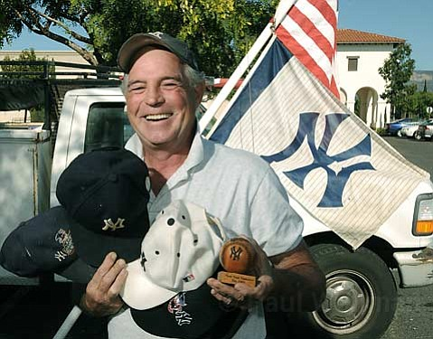 Carpinteria's Bill Connell shows his Yankee pride with five caps and a souvenir wooden baseball.
