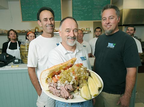 "A Three Pickles roast beef ""sub our way,"" presented by owners (from left) Bob McCourt, Bob Lovejoy, and Clayton Lovejoy at their new Goleta location."