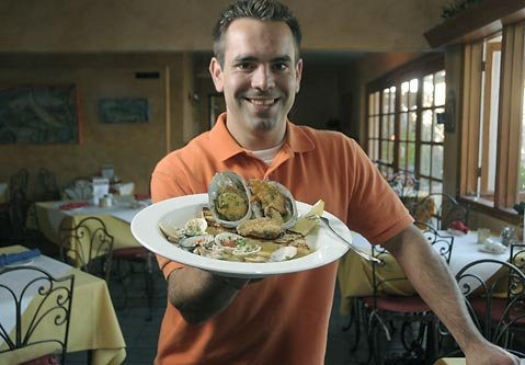 "Bay Cafe partner Harish Prather with a plate of ""Bay Abalone"""