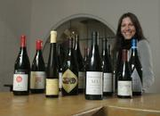 "Tasting room associate Eve Sommer-Belin with a few of the labels from the ""Friends of the Wine Cask"" wine alliance"