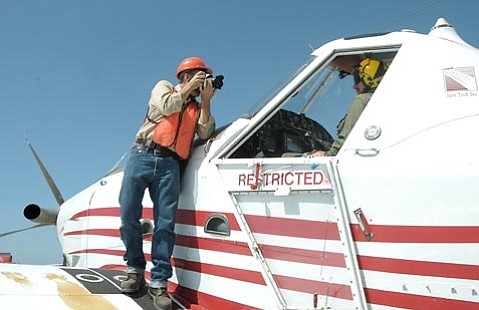 Staff Photographer Paul Wellman snaps a shot of pilot Greg Schultz at the Santa Barbara Airport in between hydromulching drops on Sept. 15, 2009