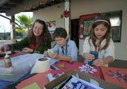 Outside (L to R) Trish Geyling, with ten-year-old son Max and seven-year-old daughter Olivia, make cards for the guests and decorations for the Rescue MIssion