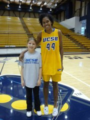 Third grader Ally Mintzer with UCSB player Mekia Valentine.
