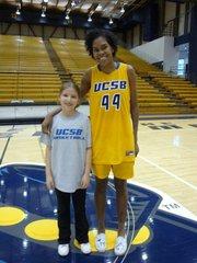 Third grader Ally Mintzer with UCSB player Mekia Valentine.