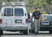 SBPD crime scene investigator Mike Ullemeyer with collected evidence from a shooting at 1535 Gillespie Mar. 1, 2010