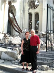 Mary and Gary Becker, residents of Santa Barbara and Board members of Fonkoze USA, in front of the destroyed catholic cathedral.