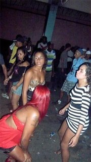 Some women scope the scene at a baile while posing in front of the DJ table.