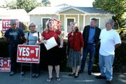 Sharon Byrne, center, speaks during the press conference yesterday held in front of the home of Sebastian Aldana, far right.