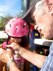 Longtime volunteer Bob Zimel helps fit a helmet for three-year-old Janet Torres.