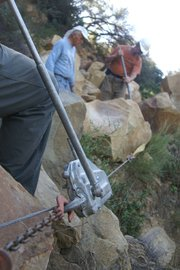 Ray Ford works a hand-cranked winch as Kalon Kelley and Rich Scholl move a boulder off the Baron Ranch Trail.