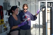 UCSB graduate student Stephanie Mendes, left, and postdoctoral researcher Molly Redmond sampling water