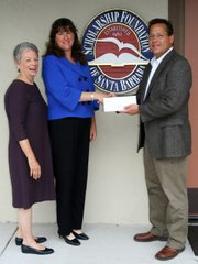 Scholarship Foundation Board Members, Kathy O'Leary and President Patricia MacFarlane, are pleased to accept a gift for scholarships from Frank Betts, ExxonMobil Superintendent.