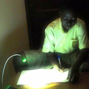 A student in Ghana completes his homework by the light of a solar-powered LED lamp designed at UCSB's Institute for Energy Efficiency