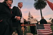 A couple attending the Dick Cheney talk last Saturday walk by protesters outside the Reagan Ranch Center