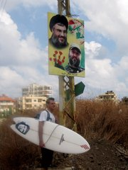 Aizenstat in Lebanon beneath a poster of Hassan Nasrallah and Imad Mughniyah.