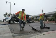 Pavement coating workers Cesar (left) and Danny finishing a slurry seal on the frontage road at Meigs Road and Cliff Drive