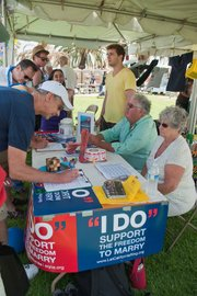 People sign petitions at the SB Equality Project booth.