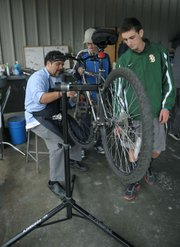 Bici Centro volunteer Eddy Gonzalez (left) and SBHS student Pete Chaconas (right) help Michael Trapani with a bike tune-up.