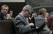 Stephen Jospeh, attorney for the Save the Plastic Bag Coalition, examines a reusable bag from Urban Outfitters