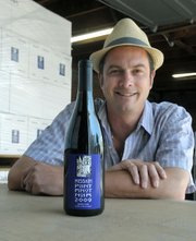 Christian Garvin, Winemaker Oreana Winemaking Company with a bottle of Mission Point Pino Noir 2009 now shipping to China (with special back labels written in chinese)