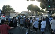 A crowd gathers as police respond to reports of a woman with a handgun barricaded in her Milpas Street apartment