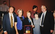 "Cash and colleagues posed with a National Blue Ribbon plaque awarded to Goleta Valley Junior High in 2000. Cash was principal there from 1995-1999. Also in the shot is Mike Couch (far right), who preceded Cash as principal at Dos Pueblos High School. Cash said that when he took over at DP, he would often ask himself, ""What would Mike do?"""
