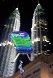 Weber pictured moments before touchdown after he helped set a Guinness World Record in 1999 for the largest-ever simultaneous BASE jump. Fifteen participants from five countries leapt from different points on the Petronas Towers in Kuala Lumpur, Malaysia. The tallest building on the planet from 1998-2004, it stands 1,483 feet tall.