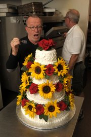 Confronted by wedding cake at Wayne Kjar Cakes, author D.J. Palladino bravely takes up his fork.