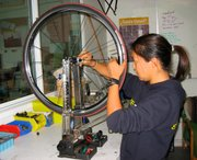 Janet Chang trues a wheel.