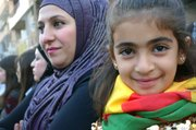 Mother and daughter attend a Kurdish rally in Derik, Syria. The girl has the colors of the Kurdish flag wrapped around her neck.
