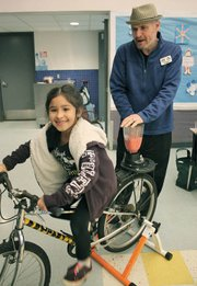 Erik Talkin, CEO of the Foodbank of Santa Barbara County, helps 7-year-old Yvonne Govea with a bicycle-powered blend at Isla Vista Elementary School as part of the Santa Barbara County Healthy School Pantry program.
